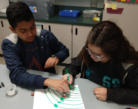 Two students setting up a paper and marble diagram of the solar system.