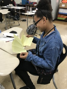 Student sitting at desk reading letter on yellow paper.