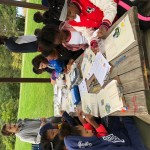 Students sitting outdoors at a picnic table, writing on a worksheet while a teacher stands nearby.