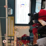 """Students facing the front of a classroom, where a slide is displayed on screen, reading """"What is a Spinal Cord Injury?"""""""