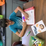 Boy wearing a turquoise T-shirt sits at a table, coloring a picture of a scientist with an orange marker.