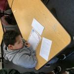 Boy wearing gray sweatshirt, looking at a handwritten letter on his desk.