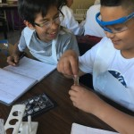 Two students wearing aprons and goggles , laughing while doing a science experiment using test tubes and pipettes.
