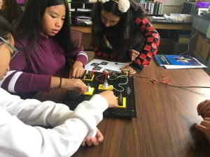 Three students doing an engineering experiment using a circuit board.