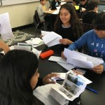 Several students at a table smiling while reading letters from their scientist pen pals. In the background, many more students doing the same.