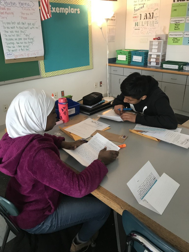 Two students reading letters from their scientist pen pals.